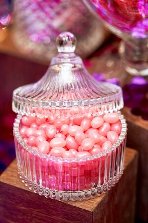 Valentines day sweets set. Colorful candies, jellies, lollipops, marshmallows and marmalade in a glass jars , close-up. A candy buffet with a variety of snacks in jars on pink background