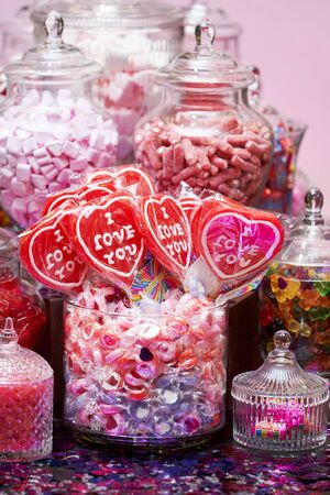 Valentines day sweets set. Colorful candies in a glass jars