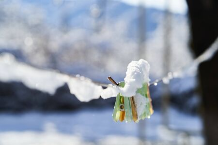 Clothespins on clothesline covered with snow, close-up, outdoors. Winter season scene, housework concept. Snowy Weather