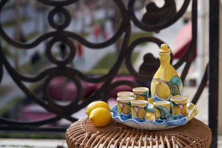 Citrus juice jug with cups on a tray, close-up. Limoncello beverage set with pitcher and drinking glass shots Stok Fotoğraf