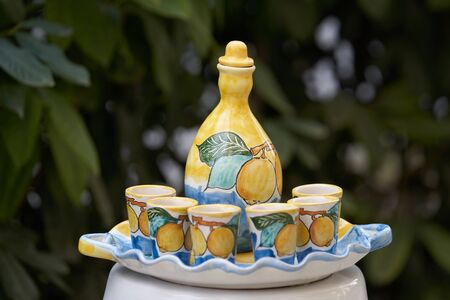 Citrus juice jug with cups on a tray, close-up. Limoncello beverage set with pitcher and drinking glass shots Banco de Imagens