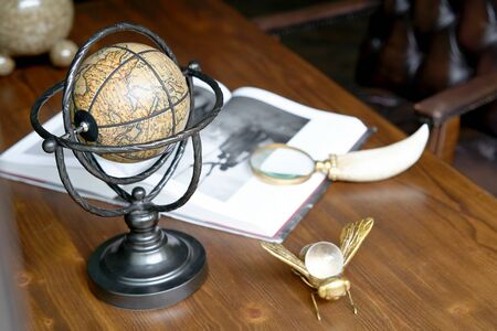 Education and travel concept. Travel or adventure background with antique globe, magnifying glass and book on table. Banco de Imagens