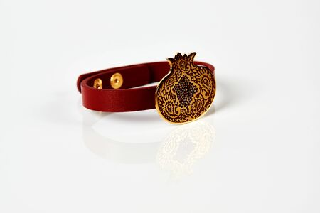 Red leather and gold cuff bracelet on white background with copy space. Female precious bracelet with gemstone jewelry, close-up. Bangle jewelry