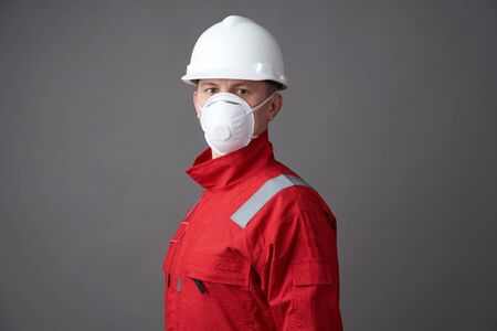 Young engineer worker wear a helmet, face mask and protective workwear suit. Worker man wearing hygienic mask, overall and protective hard hat. Coronavirus pandemic quarantine hygiene, Safety first Stock Photo