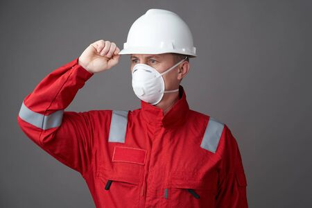 Worker man wearing hygienic mask, overall and protective hard hat. Young engineer worker wear a helmet, face mask and protective workwear suit. Coronavirus pandemic quarantine hygiene, Safety first