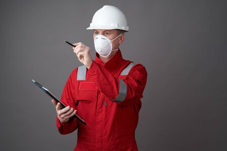 Man engineer, construction worker wearing face mask and workwear uniform are checking the list on the clipboard over grey background with copy space. Coronavirus pandemic quarantine hygiene, Safety first Standard-Bild