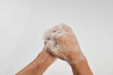 Man washing dirty hands with soap, close-up. Soapy male hands isolated on white background with copy space.  Hand washing medical procedure step. Personal hygiene