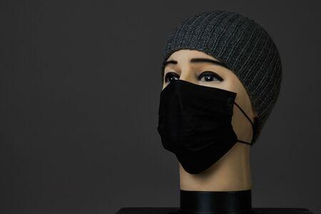 Tête de mannequin avec masque facial sur fond noir avec espace de copie. La tête en plastique d'un mannequin masculin porte un masque de chirurgie médicale en tant que concept de coronavirus de quaranrine pandémique. Banque d'images