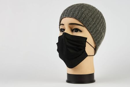 Mannequin head with face mask on white background with copy space. Plastic Head of a male mannequin wear medical surgery mask as pandemic quaranrine coronavirus concept.