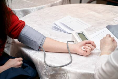 Doctor checking patient arterial blood pressure, close-up.