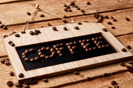 Coffee shop chalkboard frame. Blackboard with COFFEE text by coffee beans on wooden wall background. Hanging door sign board Standard-Bild