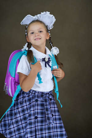 Student girl with school backpack. 6 years old girl with schoolbag on dark background, close-up. Back to school concept