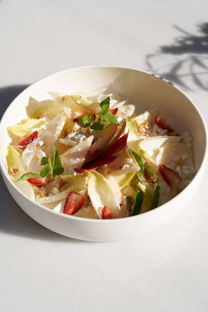 Endive salad with goat cheese, strawberry and walnuts. Belgian endive leaves salad on table Archivio Fotografico