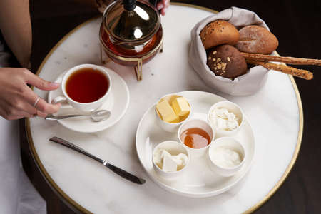 Healthy breakfast set on table with honey, tea, bread and butter Banco de Imagens