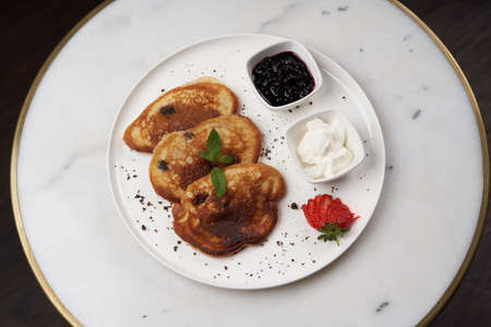Pancakes with fresh berries and jam. Healthy breakfast table with Crepes, blueberries, strawberry and yoghurt