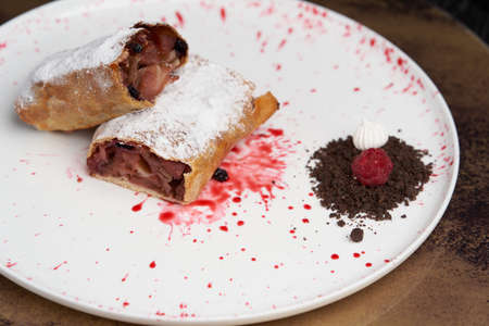 Strawberry biscuit roll with berry syrup and fromage frais. Strawberry roll cake on white plate on table Banque d'images