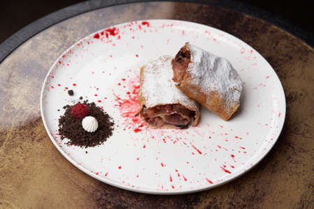 Strawberry biscuit roll with berry syrup and fromage frais. Strawberry roll cake on white plate on table