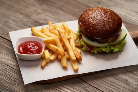 Big burger and fries. Hamburger with french fries and ketchup on wooden table background with copy space. Fast food menu