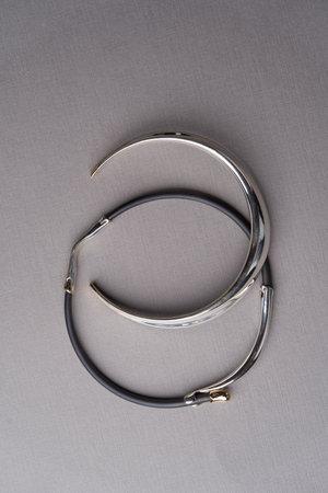 Women's jewelry bracelet. Precious bangle jewelry on gray background with copy space