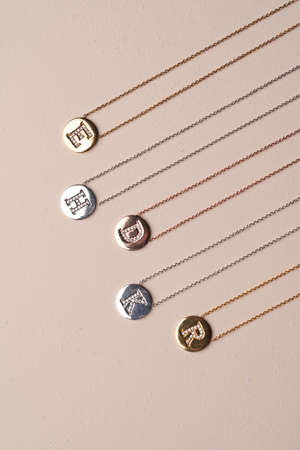 Gold Letter Necklace. Gold chain with pendant, close-up