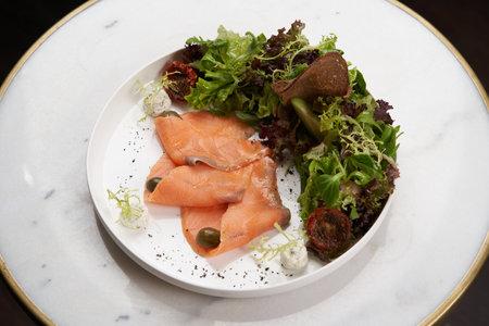 Smoked salmon salad. Healthy salad with vegetable and smoked salmon on a white plate on table