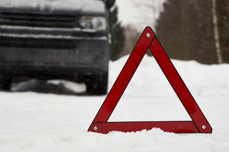 Car with a breakdown on snowy road. Winter driving, warning triangle on a winter road Imagens