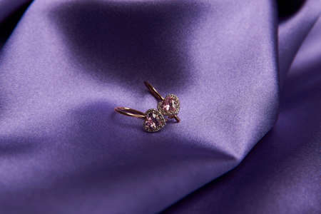 Heart diamond earrings on purple background, close-up. Heart shaped gold earrings with pink gemstone on violet silk background Reklamní fotografie
