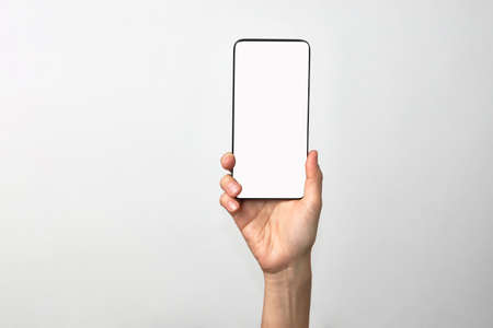Woman hand holding phone on white background with copy space. Woman holding smartphone with white screen. Hand with blank cellphone display, close-up