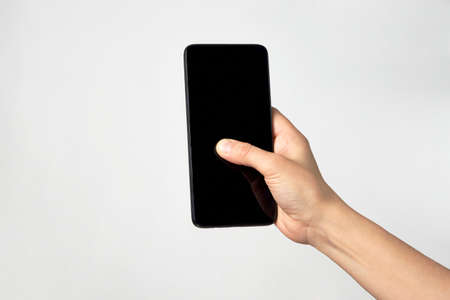 Woman hand holding phone on white background with copy space Reklamní fotografie