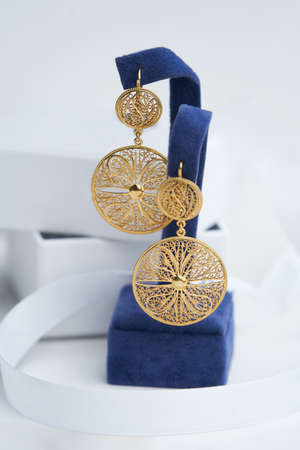 Vintage earrings on white background with copy space, close-up. Golden earrings on display stand Reklamní fotografie