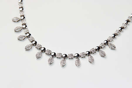 Elegant necklace with diamonds on white background with copy space. Women's platinum necklace with a precious gemstones, close-up. Elegant female jewelry Reklamní fotografie