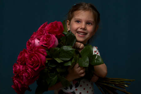 Little girl with a flowers bouquet. Cute baby girl with bouquet of roses flowers on dark background with copy space, close-up portrait