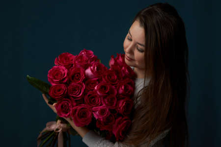 Beautiful woman with a flowers bouquet. Young woman holding bouquet of roses flowers on dark background with copy space, close-up portrait Foto de archivo