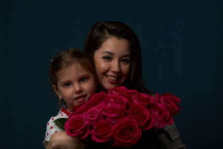 Happy mother and daughter with flowers . Mother and daughter holding bouquet of roses flowers on dark background with copy space, close-up portrait Foto de archivo