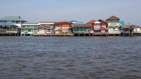 stilt house: Traditional stilt houses located at the riverbank of Bangkoks Chao Phraya. A wooden ladder is leading down to the water.