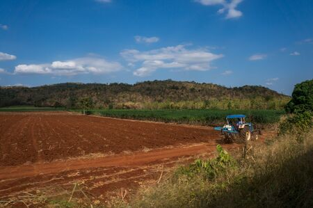 red soil: Red soil and manioc fields in Kanchanaburi province, Thailand with mountains in the background. A tractor is driving on the soil.