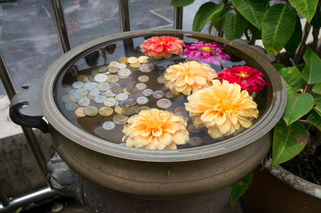 A small floral wishing well with coins on Penang Hill, Malaysia Zdjęcie Seryjne
