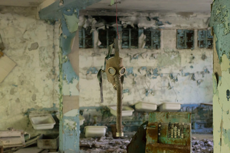 cash register building: A gas mask is hanging from the ceiling in an abandoned house in Chernobyl after the nuclear catastrophe Stock Photo