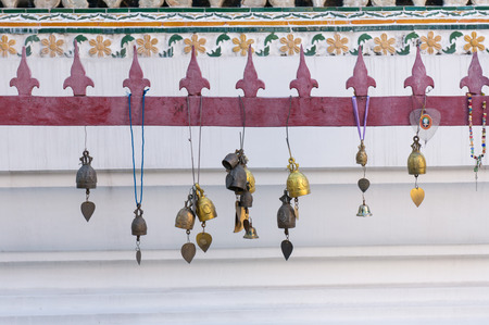 Golden bells and decorations hanging in front of a temple in the buddhist Wat Arun, Bangkok Фото со стока