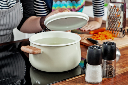 Opened white saucepan with wood pens on the black stove and glass spice mill in the kitchen room. Cooking a soup, preparation. Woman's hand