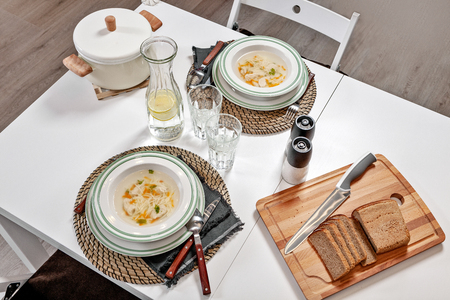 Chicken noodle soup served with brown bread and lemonade for two persons. Top view