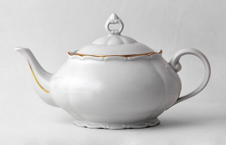 White teapot with golden rim in classic style isolated on white background