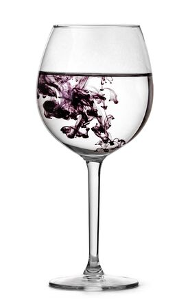 Glass with water and drop of violet ink. Half full glass for wine isolated on white background with clipping path