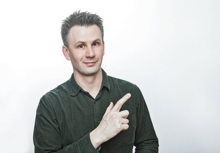Confident young man pointing finger aside at blank copy space advertising unbelievable presentation, astonished surprised guy looking at camera isolated on white grey studio background