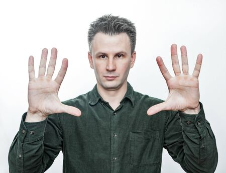 Magic trick. Photo portrait of a young european man showing both of his opened palm. Isolated on white background