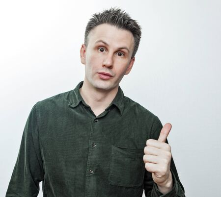 Shocked stunned young man pointing finger aside at blank copy space advertising unbelievable presentation, astonished surprised guy looking at camera isolated on white grey studio background Stock fotó