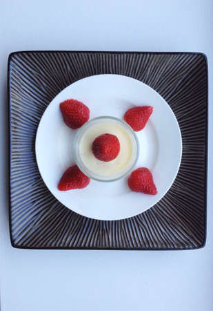 appetising: Strawberries arranged on a white plate around a cream pot to make an appetising dessert