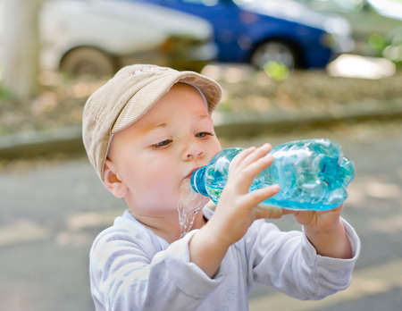 hand holding bottle: Young boy drinking water from plastic bottle
