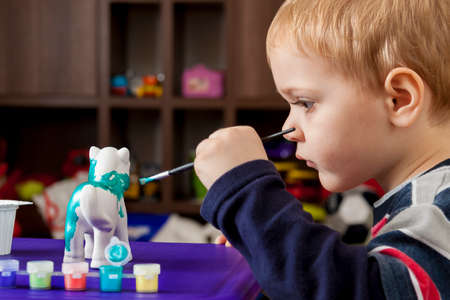 caucasian children: Boy painting ceramic figure