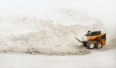Snow removing yellow bulldozer near big snow piles